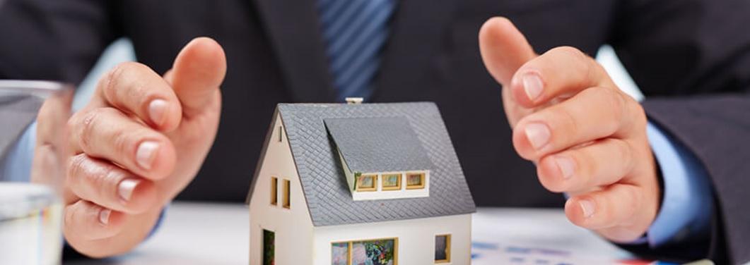 Photo petite maison entourée de mains protectrices